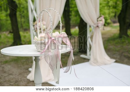 Cute wicker baskets with bows and peony petals inside, on small white table. in front of wedding arch