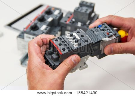 electrician's hands holding a residual current device