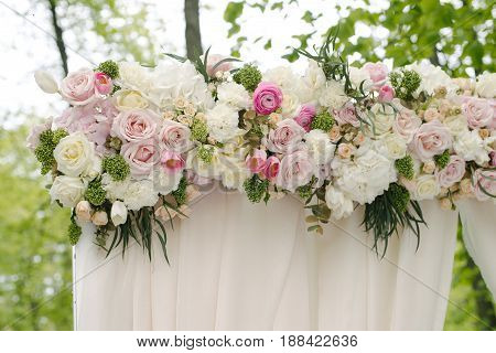 Beautiful wedding archway. Arch decorated with beige cloth and flowers, outdoor