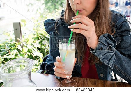 Young smiling girl drinking tasty sweet cocktail , amazing relaxing day, tasty lemonade, outdoor terrace