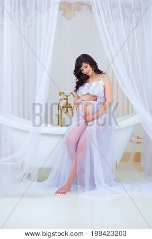 Gentle pregnancy. Beautiful pregnant in light white dress with orchids.