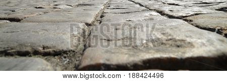 Road paved with old stones close view texture