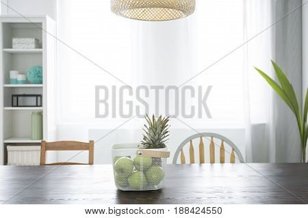 Dining room with wood table bookcase rattan lamp and window