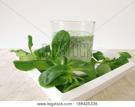 Green smoothie with corn salad in glass