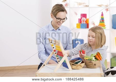 Tutor And Girl Counting With Abacus