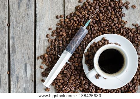 Syringe, a Cup of coffee and coffee beans on wooden background