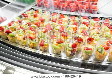 Fruit salad arranged in plastic cups for sale. refrigerator showcase or buffet. Used in cocktails and as a topping to the chocolate fountain.