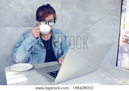 young woman working on laptop and drinking coffee at cafe