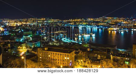 night view of the city, a lot of lights ships and reflected glare on the water.beautiful night city