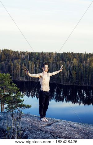 middle age man doing sport yoga on the top of the mountain, lifestyle people outdoor, summer wild nature for training close up
