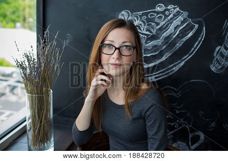 Girl In Glasses And Gray Dress Sitting In Cafe