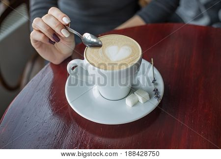 Hands Holding Teaspoon Over Cup Of Coffee With Foam