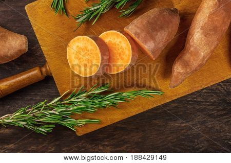 An overhead photo of slices of sweet potatoes with branches of fresh rosemary, shot from above on dark wooden textures with a place for text