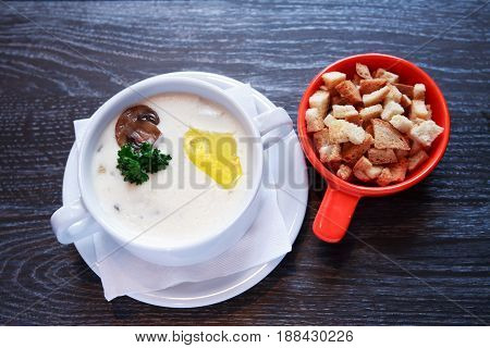 Bowl with mushroom soup in white bowl on dark wooden table