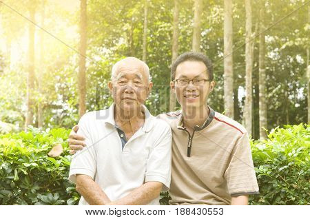 Happy senior man and his son relaxing in the garden.