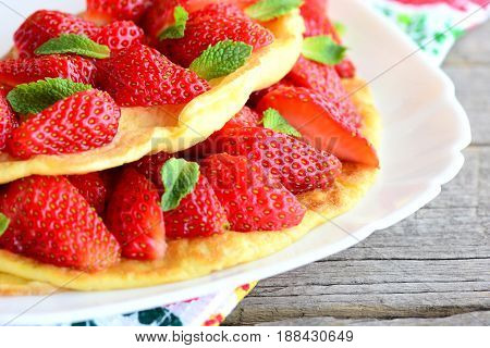 Sweet strawberry omelet. Delicious omelet stuffed with strawberries and garnished with mint on a plate. Fresh strawberries on old wooden table. Summer breakfast omelette recipe. Closeup