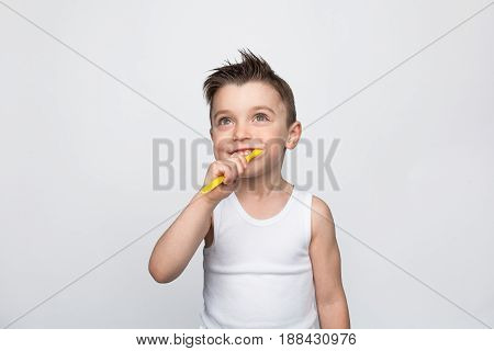 Boy in white tank top brushing teeth smilingly and looking up on studio background.