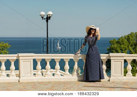 Young woman taking pictures on a smart phone on the waterfront near the sea. Selective focus.