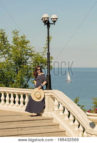 Young woman in a long dark blue skirt on the waterfront near the sea. Selective focus.
