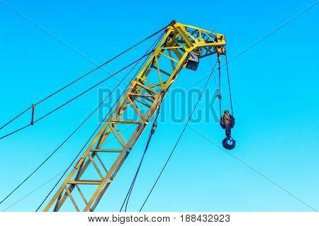 Modern construction crane against blue sky background