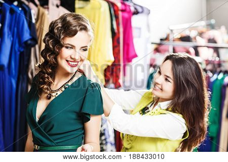 Beautiful woman trying on clothes with women assistant at shopping mall indoors
