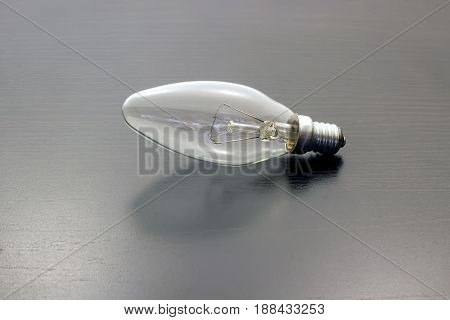 Light bulb turned off over black wooden background