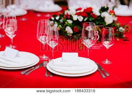 Numbered guest table on wedding ceremony, decorated with bouquet and settings, in white and red colours