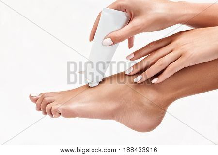 Woman squeezing moisturising cream on her leg over white background. Healthy feet concept.