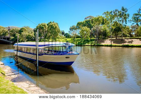 Tourists boat in Adelaide city anchored near King William road in Torrens river on a bright day