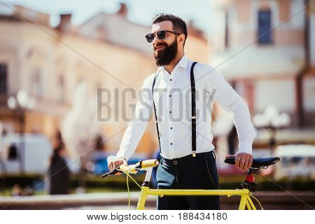 Young Stylish Man Going To Work By Bike. Hipster With A Fixie Bicycle On The Street. Bearded Man Loo