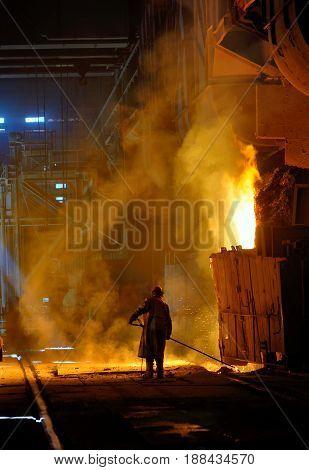 steel worker near oven inside of steel plant