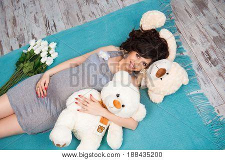 Beautiful pregnant mother with teddy bears. Motherhood.