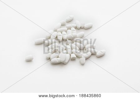 Top view of group of white pills isolated on white background