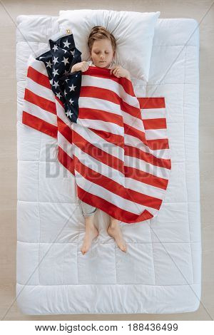 US flag. Pleasant cute small boy lying on the bed and being covered with the US flag while having patriotic dreams