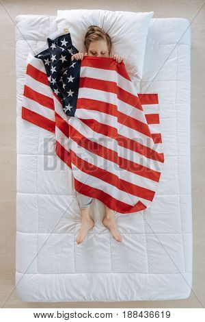 My native country. Nice cute pleasant boy being covered with US flag and having pleasant dreams while being a US patriot