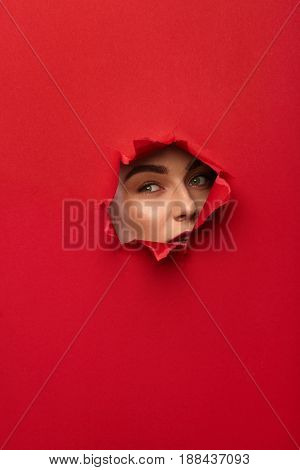 Young woman looking through a hole in red colored cardboard. Vertical studio shot.