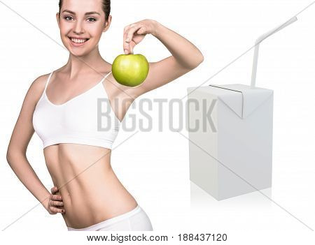 Happy young woman holds an apple near juice box template. Healthy eating concept.