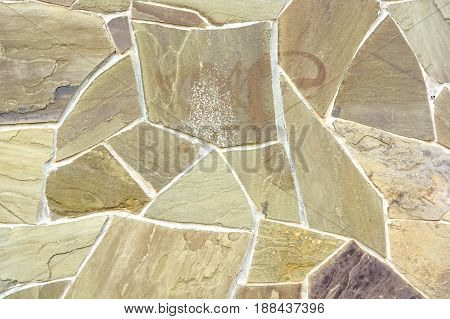 Close up beige stone wall made of fragments