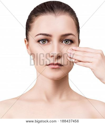 Young woman applying powder on her face with sponge isolated on white.