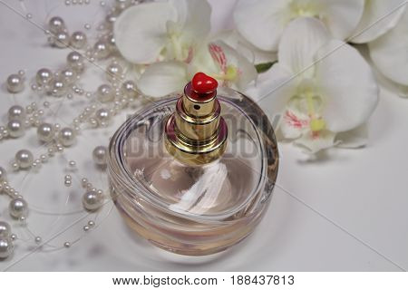Perfume/ Bottle of perfume with pearls, white orchid and red heart.