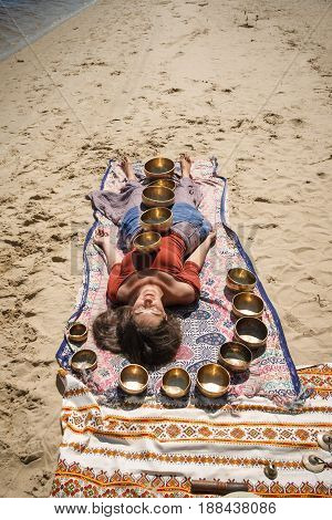 A woman is relaxing with singing bowls on her body lying on a river bank on a sand beach