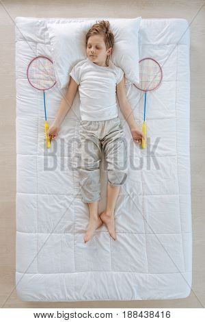 Ready to play. Delighted positive nice kid lying on the bed and holding badminton rackets while being ready to play badminton
