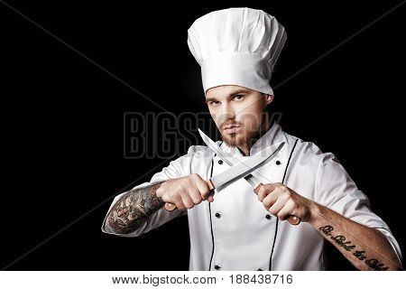 Young bearded man chef In white uniform holds Two knives on a black background