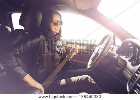 Brunette in sunglasses woman fastens with a belt in an expensive car. Safety first. Beautiful caucasian lady fastening car seat belt.