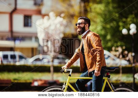 Young Bearded Man Adjusting Eyewear And Looking At Camera While Sitting On His Bicycle Outdoors