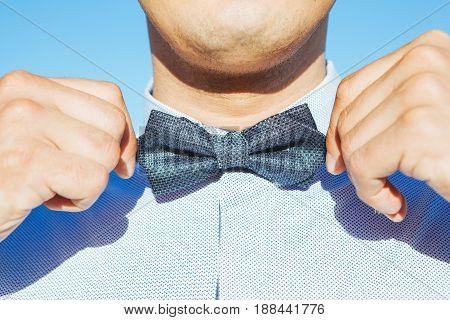 the man straightens a bowtie on his skirt