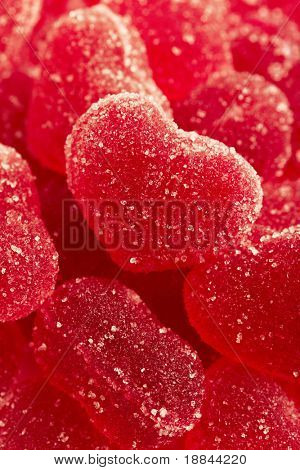 Red fruit candy in the form of the heart, strewed by sugar