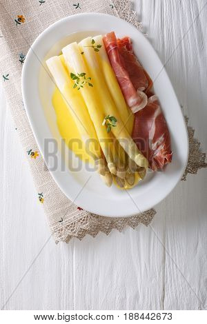 White Asparagus With Hollandaise Sauce And Ham Close-up On A Plate. Vertical Top View