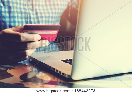 Young Asian Man Holding Credit Card With Using Laptop And Online Shopping Or Internet Banking Concep