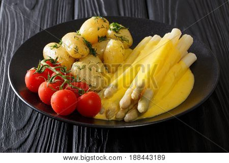 White Asparagus With Hollandaise Sauce, New Potatoes And Tomatoes Close-up. Horizontal